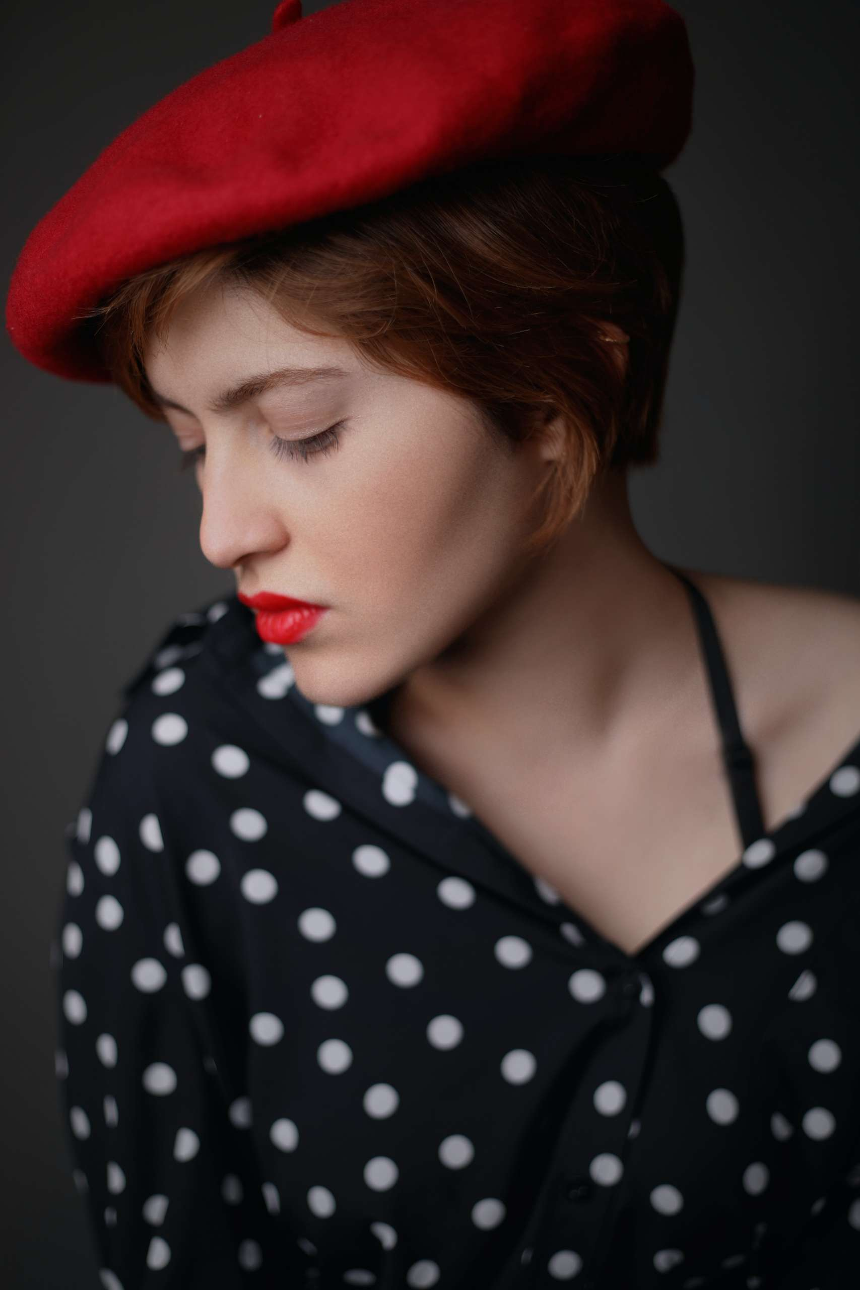 woman wearing red newsboy hat and black and white polka-dotted button-up top
